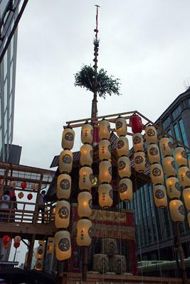 雨の夕方に淡く提灯が光る、京都・四条烏丸西の祇園祭の山鉾「函谷鉾」と両側のビル