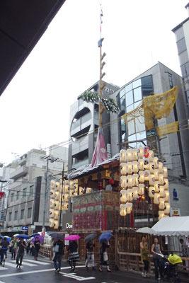 京都・四条室町にある雨下の祇園祭の山鉾「鶏鉾」と、統一感なく意匠もおかしい背後のビル