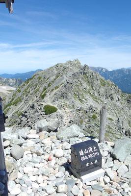 立山雄山山頂の雄山神社・峰本社にある「雄山頂上」の石碑と登拝者が持ち込んだ玉石、そして対面に聳える立山最高峰の「大汝山」