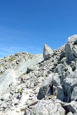 立山山頂の三峰の内、中央の最高峰「大汝山(おおなんじやま。3015m)」と右側(南)の雄山(3003m)の間を巻く、岩が散らばる登山路と、その傍にある尖った大岩