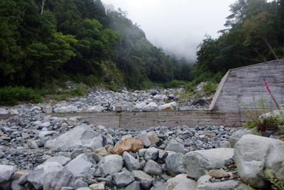 新穂高温泉から続く右俣林道の終点「白出沢」の水のない河原と岩が乗り上げる堰堤