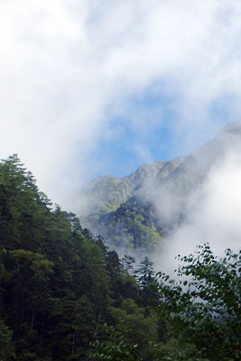岐阜県・新穂高温泉からの槍ヶ岳登山道途中のチビ谷から見えた、靄の中から姿を現す、槍ヶ岳南の中岳とその西尾根辺りの北アルプス山上