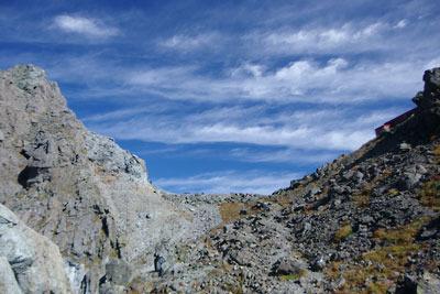 槍ヶ岳山頂(左端)と槍ヶ岳山荘(右端)の間に接する西鎌尾根道の端部