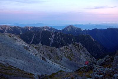 落日により淡色に暮れなずむ、東方は槍沢及び大天井岳(おてんしょうだけ。中央右の峰)方面