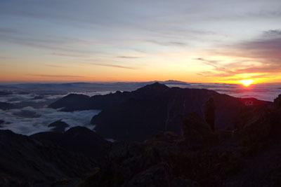 槍ヶ岳のテント場から見た、東方の笠ヶ岳や白山の傍に落ちる夕陽