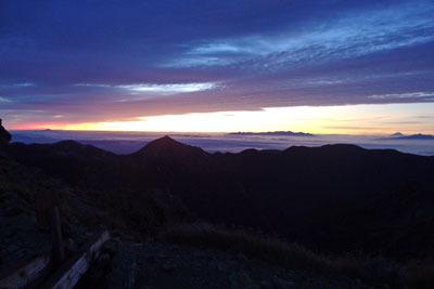 槍ヶ岳山荘付近から見た、東方の槍沢(上高地源流)や大天井岳(おてんしょうだけ。中央左)方面と、彼方で光る日の出前の空