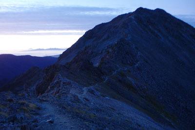 槍ヶ岳山荘のテント場から見た、日の出前の薄明に佇む大喰岳