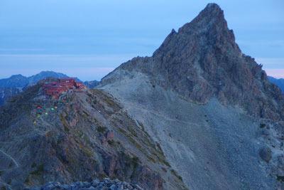 北アルプス・大喰岳山頂から見た、日の出直後の槍ヶ岳と槍ヶ岳山荘及びテント場(左山上)