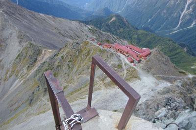 槍ヶ岳山頂穂先の、最後の梯子上から見た下方の槍ヶ岳山荘や飛騨沢。実は彼方(画像中央上)に麓の起点「新穂高温泉」も見えている