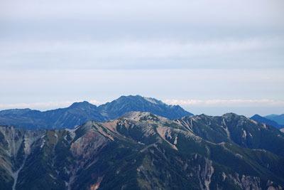 槍ヶ岳山頂にある祠越しの北方彼方に見えた立山と剱岳