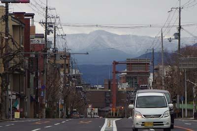 銀閣寺道交差点から見た、上部に雪を纏い京都市街彼方にはだかる愛宕山