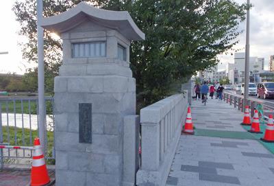 改修工事で石材が磨かれた賀茂大橋の親柱・高欄と設置工事中の歩道安全柵