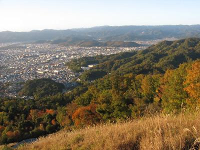 大文字山山腹の「五山送り火」の火床からみた京都市街北部や夕陽に照らされる山の紅葉