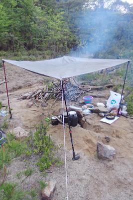 野営地の炉の上に設けたストックとシートやロープを使った夜露・朝露除けの屋根