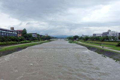 朝の強雨の影響を夕方まで宿す京都・賀茂川(鴨川)の濁流