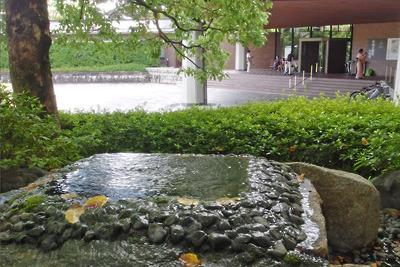 泉屋博古の庭にある自噴井戸越しに見た閉館直後の博物館玄関と、浴衣でゆかた展に来た参観者らの姿