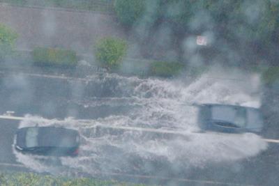 2021年8月14日朝の豪雨で冠水した滋賀県大津市の道路と舟のように水を分けて行き交う自動車