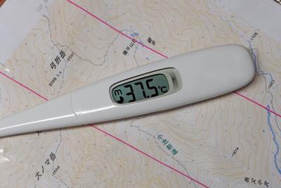 北アルプス鏡平付近の1/25000地形図上に置かれた副反応熱37.5度を示す体温計